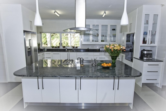 Painted high gloss white kitchen with isand unit with gas and electric hob as well as a double door fridge and double eye level oven