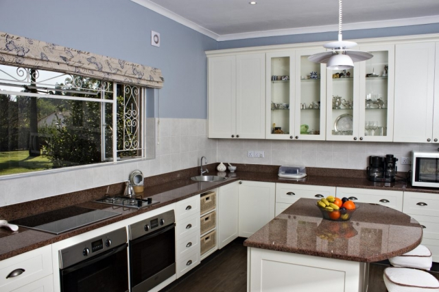 White painted shaker kitchen untis with 2 undercounter ovens and gas and electric hob, central island can seat two people
