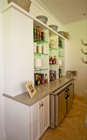 MDF painted white raised panel bar with ceaserstone countertop and glass shelving