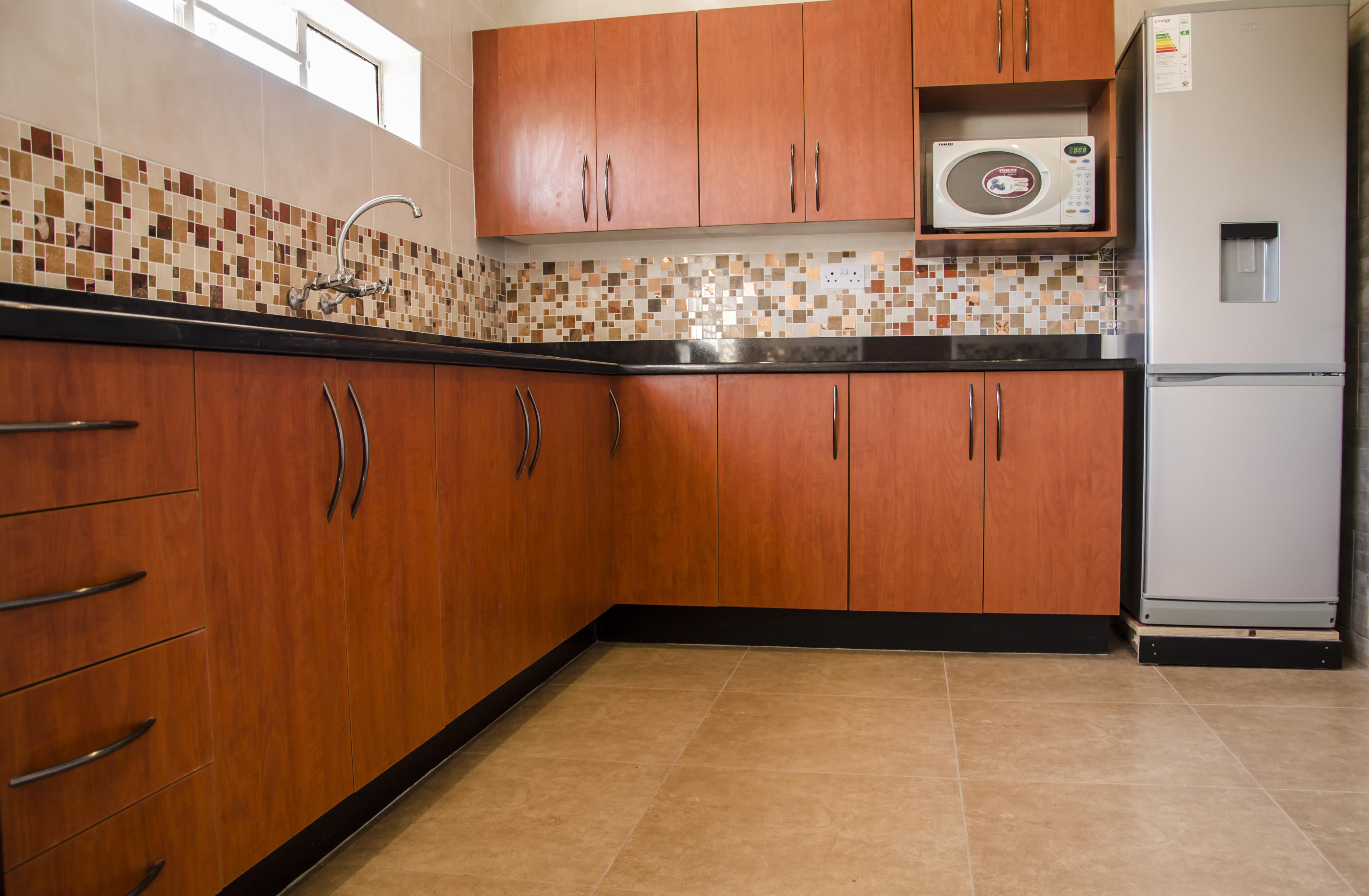 Cherry royal melamine kitchen with double sink and wall mounted microwave with free standing fridge