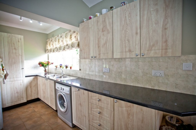 Amber oak PVC wrappe kitchen with local granite tops double sink and washing machine