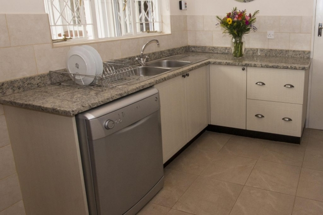 PVC wrappe scullery with double sink and dishwasher and units with buttercup handles